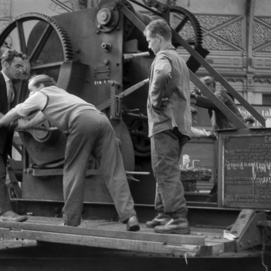 Three men co-operate to turn a huge cog-wheel on some track machinery in a railway station, circa 1960