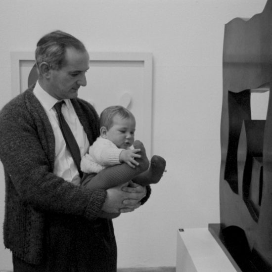 A man holds a baby in front of a Henry Moore sculpture during an exhibition at Arts Council Gallery in Cambridge, England, circa 1962