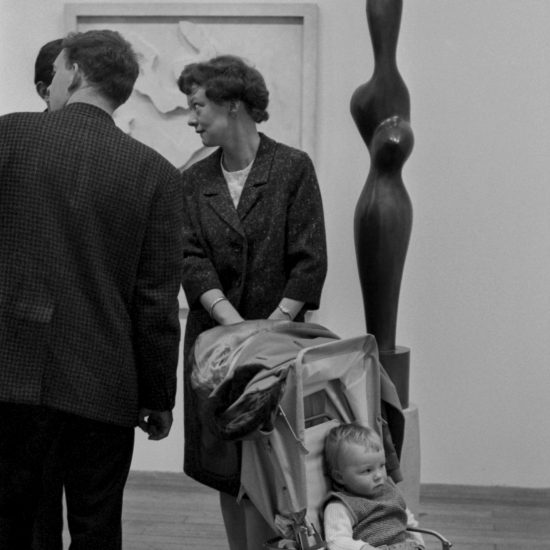 A woman and a child in a pushchair look at the Henry Moore sculptures during an exhibition at the Arts Council Gallery in Cambridge, circa 1962