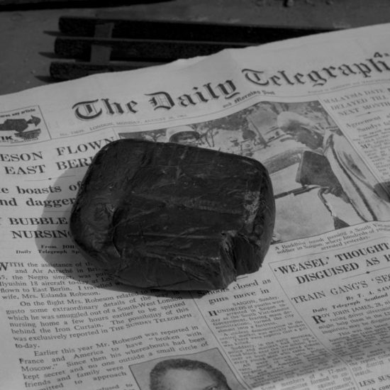 A large block of hash rests on a copy of The Daily Telegraph from 1963