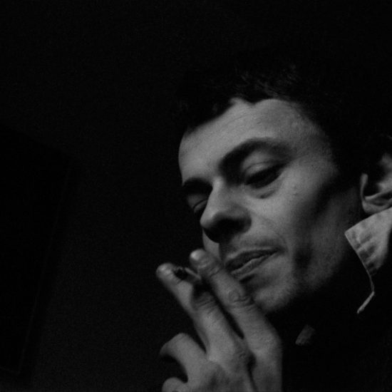John Hoppy Hopkins portrait holding cigarette, with black background, circa 1962, west London