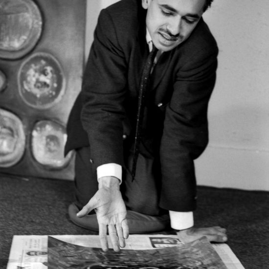 Iqbal Geoffrey, Pakistani abstract painter, kneels on the floor and gestures at one of his paintings in London, circa early 1962