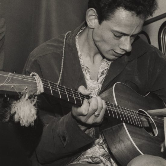 Hoppy plays guitar aboard the Pyne T-V bus, before a press reception, summer 1957
