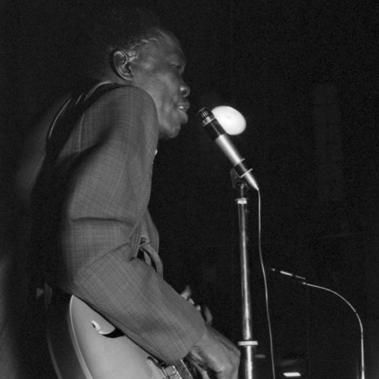 John Lee Hooker sings into the microphone during The All Night Rave at Alexandra Palace, 26 June 1964, shot from the stage. Hooker is viewed in profile, whilst singing and playing the guitar, and the audience is just visible in shot