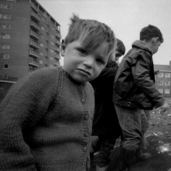 Four small boys play on a piece of waste ground surrounded by new-build blocks of flats, London, circa 1962