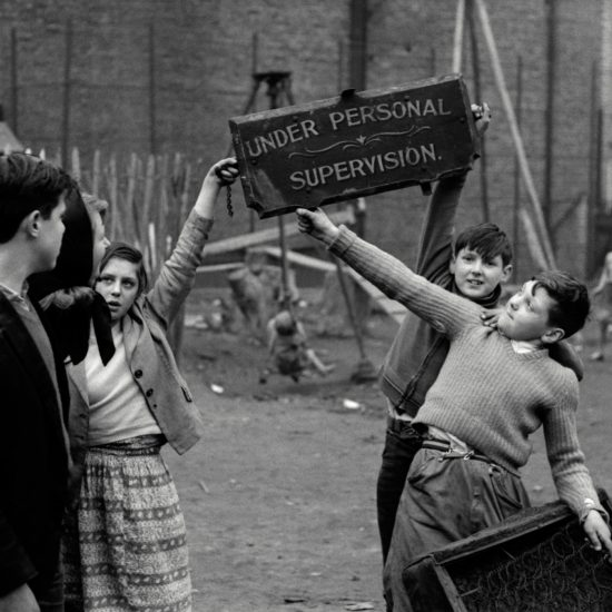Children play on a cleared bomb site and hold up a sign from a shop marked Under Personal Supervision on derelict land in Notting Hill, West London