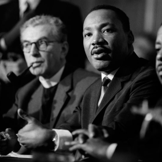 Canon Collins points at someone out of shot and MLK gestures as he speaks at a London press conference at the Hilton Hotel, organised by CND in December 1964. L-R: Canon Collins, Martin Luther King Jr., Ralph Abernathy