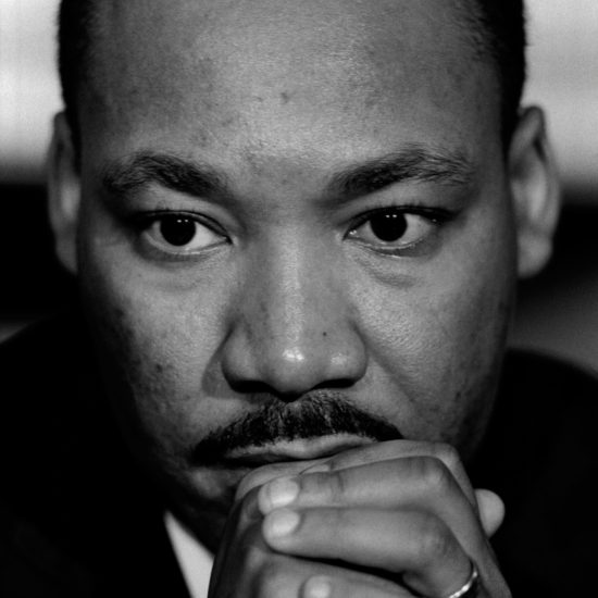 Martin Luther King Jr. rests his chin on his hands at a London press conference at the Hilton Hotel, organised by CND in December 1964; shot in close-up