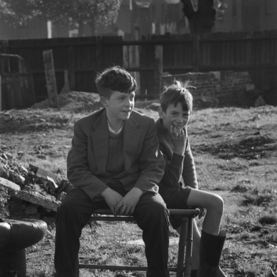 Two boys sit on a metal frame in an area of waste ground behind some houses in Kingston, West London, circa 1961. One boy waers a suit jacket, long trousers and shell-toe trainers; the other wears a jumper, shorts and wellington boots