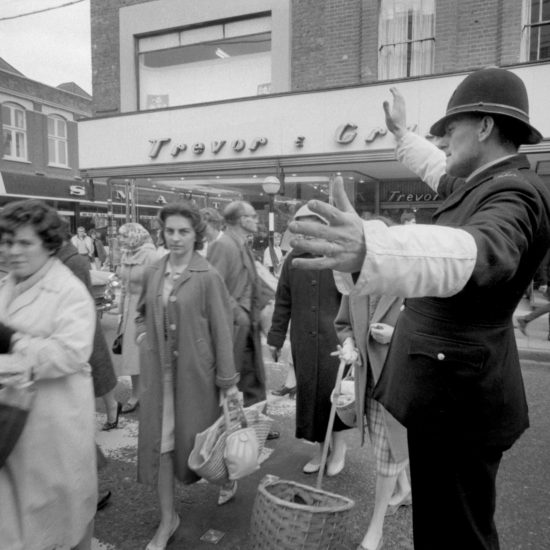 A police constable directs shoppers across the road in Kingston market, west London, circa 1961