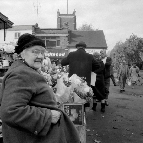 An older woman stands by a flower stall in Kingston market, west London, circa 1961