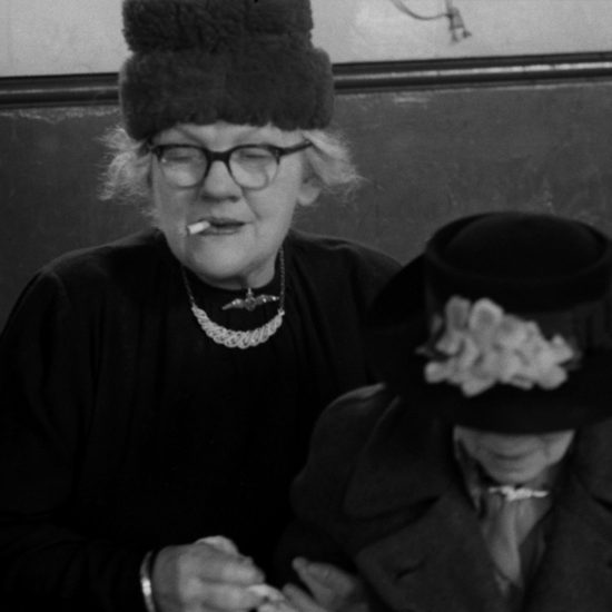 Two elderly women wearing hats sit beside each other in Kingston, West London, circa 1961. One woman wears glasses and is smoking a cigarette
