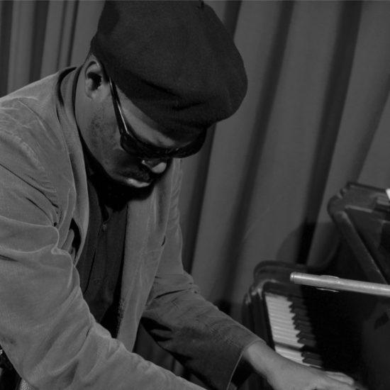 American jazz multi-instrumentalist Rahsaan Roland Kirk plays piano during a rehearsal at Ronnie Scott's, circa 1963