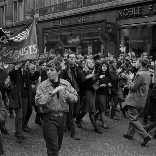 People gesticulate, clap, sing and carry a Federation of London Anarchists banner as they pass Noble Furs of Regent Street on the way to Hyde Park and the end of the 1963 Aldermaston to London march, circa 1963