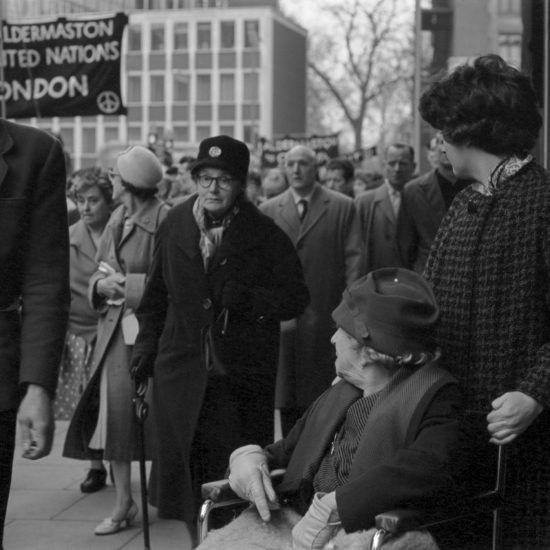 Two women, one in a wheelchair, watch as the Aldermaston to London March of April 1962 passes them on a London street