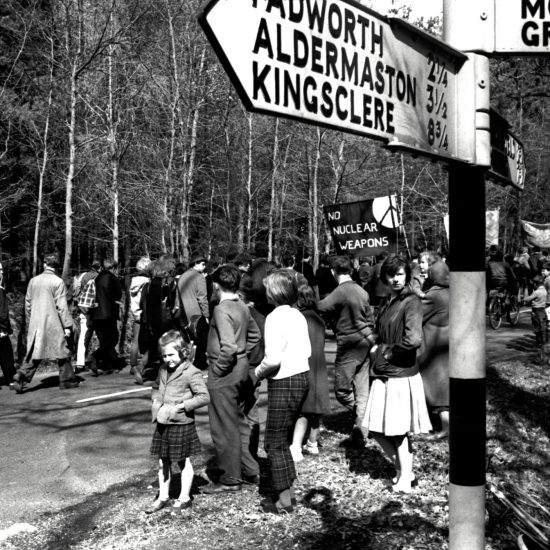 Demonstrators walk past a road sign to Aldermaston and local spectators during the 1963 Aldermaston to London march