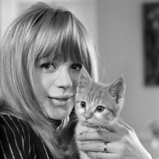 Marianne Faithfull smiles at the camera whilst holding a kitten, London circa 1965