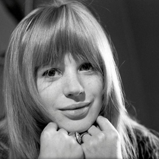 Marianne Faithfull smiles at the camera with her chin in her hands, photographed in close up