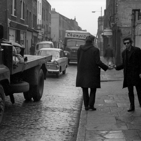 Two young men conduct a drugs transaction in the street in the East End of London, circa 1962