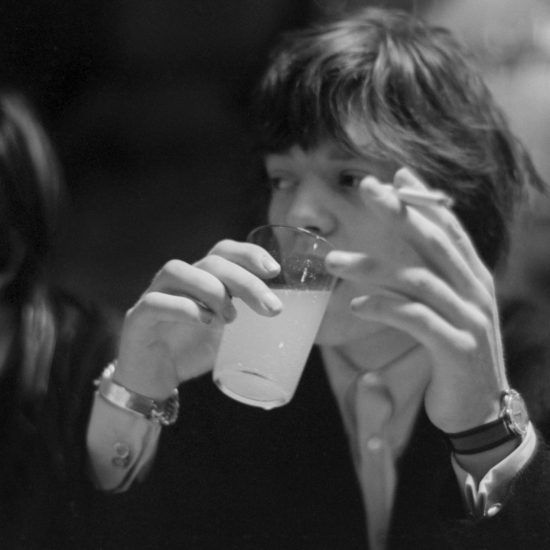 Keith Richards (left) and Mick Jagger (right) of the Rolling Stones sit together at a cafŽ table. Mick drinks from a glass and holds a cigarette in his left hand
