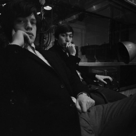 In 1964, Mick Jagger and Charlie Watts of the Rolling Stones relax in the studio during a photo shoot