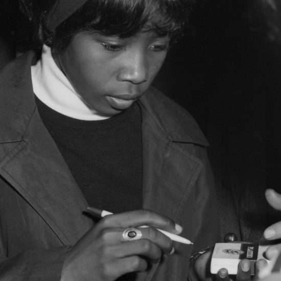 Millie Small, the Jamaican singer-songwriter who sang 'My Boy Lollipop', signs her autograph on a packet of cigarettes before performing onstage at The All Night Rave at Alexandra Palace, 26 June 1964
