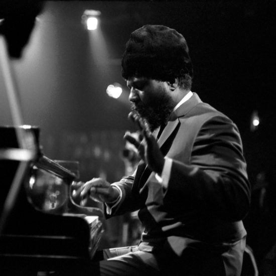 American jazz pianist and composer Thelonious Monk plays piano on stage at the Marquee Club in Wardour Street, London, during a recording of the BBC-TV Jazz 625 programme on March 14, 1965. Technicians can be seen in the background