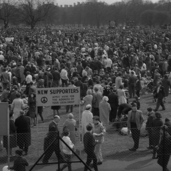 A fenced-off area in a park in London is full of people, during the Aldermaston to London anti-nuclear march in April 2962. A sign with a CND logo on it says 'New Supporters - Apply here for the address of your local group'