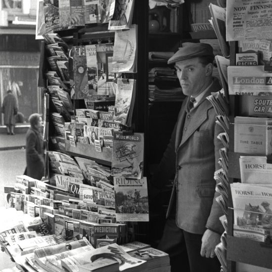 A white male stands in the doorway of a newsagents in London in February 1960. He wears a three piece tweed suit and a flat cap, and is surrounded by contemporary magazines and newspapers for sale