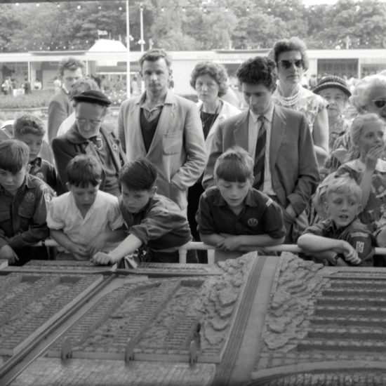 Children and adults crowd around a large tableau in a marquee during the Festival of Labour in Battersea Park