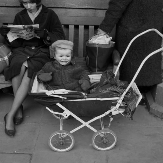 A warmly-dressed child in a pram wearing a CND badge looks unhappy whilst women read newspapers on a bench behind the pram, Oxford, circa 1963
