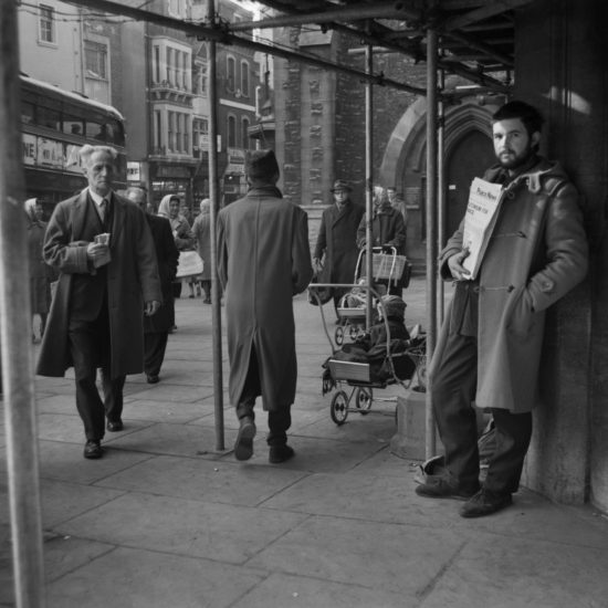 Richard Wallace stands on a street corner in Oxford, selling copies of Peace News. A double decker bus passes in the background, and a police constable walks through  the shot. A child in a pram can be seen in the background, circa 1963. Wallace was subsequently jailed for 4 weeks for 'obstructing the highway'.