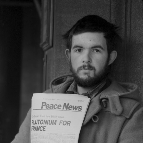 Richard Wallace sells Peace News in Oxford, wearing a duffel coat, circa 1963. The headline reads 'Plutonium for France'. Wallace was subsequently jailed for 4 weeks for 'obstructing the highway'.