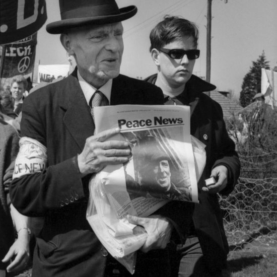 An older white male, weating a trilby and carrying a copy of Peace News, accompanies the 1962 Aldermaston to London march