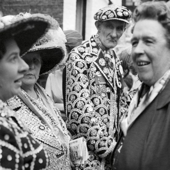 A Pearly King and Queen look on with disapproval as two women chat in the street, East London, circa 1964