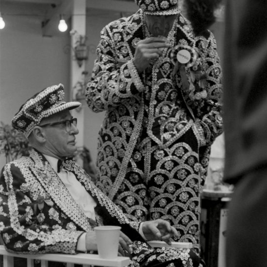 A pearly king wearing a Hammers rosette stands next to a pearly king seated in a chair at an East End social function, east London, circa 1964