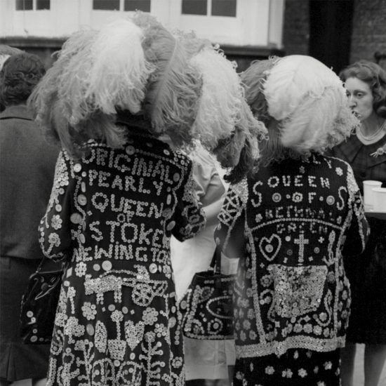 The pearly queens of Stoke Newington and Bethnal Green show off the backs of their outfits and their luxurious plumed hats during a social function in London's East End, circa 1964