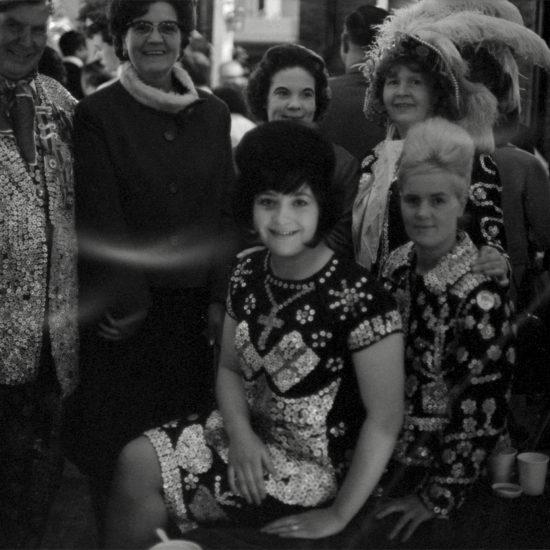 Two young pearly queens with beehive hairstyles pose with other pearly kings and queens at a social function in the East End of London, circa 1964
