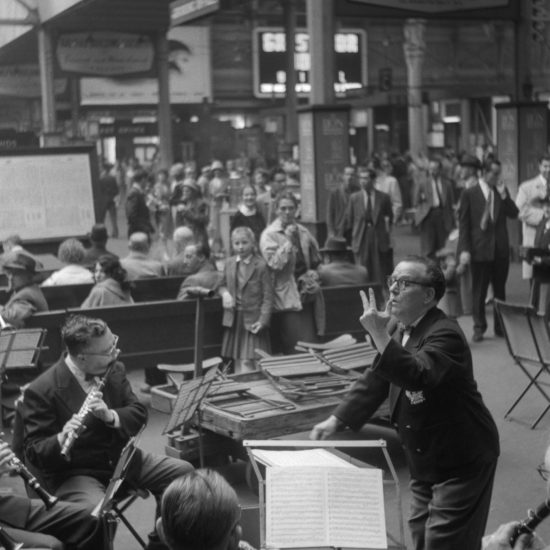 A small orchestral band with a conductor plays on a train station concourse in front of crowds of passengers, including school children, circa 1960