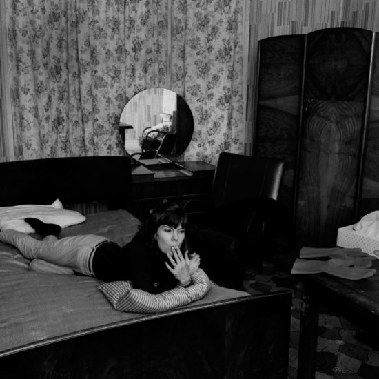 A female sex worker in Notting Hill (Cree), lying on a bed with rubber gloves and tissues in the forground