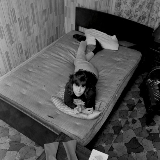 A female sex worker in Notting Hill (Cree), lying on a bed and smoking, with rubber gloves and tissues in the foreground, London circa 1964