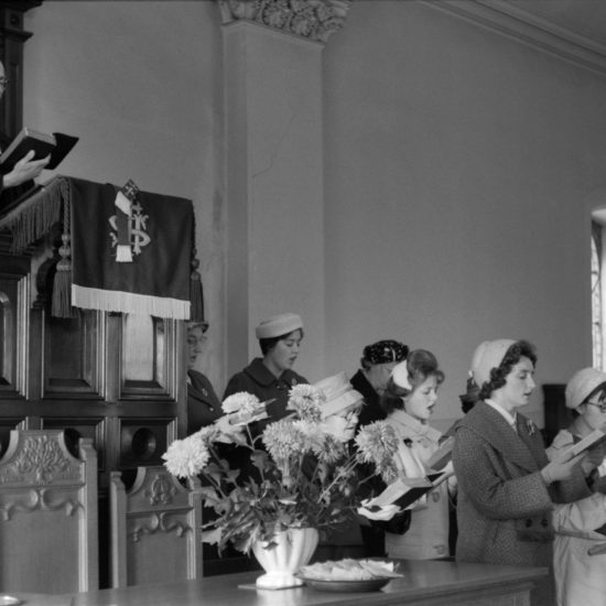 The priest in his pulpit and members of the congregation in the choir stalls sing hymns in their parish church situated in Kinglassie mining village, Fife, Scotland, circa 1963