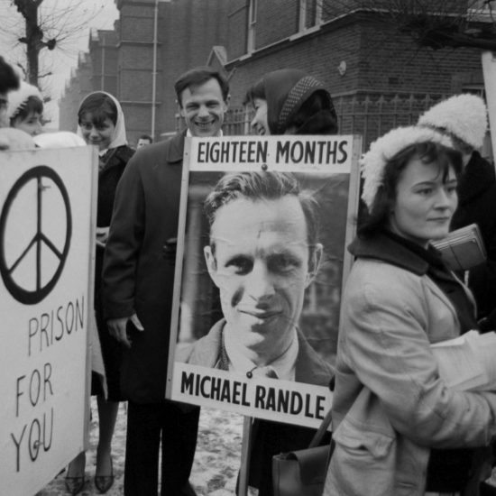 Dr. Michael Randle is surrounded by supporters and banners on his release from Wormwood Scrubs in the winter of 1963, having completed his prison sentence for his part in organising nonviolent direct action at a USAF Wethersfield, as a member of the Committee of 100. A man holds a banner with a CND logo and the legend 'In Prison For You', whilst a woman holds a banner with Randle's face on it
