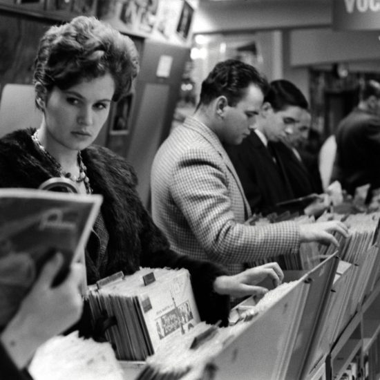 """A smartly dressed woman looks off camera as she flicks through racks containing pop music 7"""" vinyl records in a record store in 1962. She is surrounded by men looking through the racks of records"""