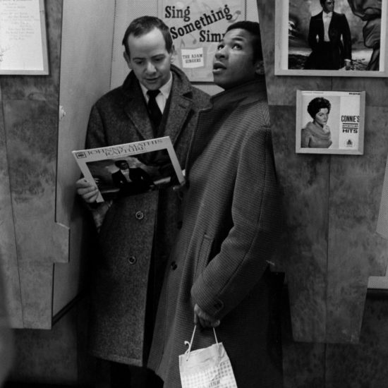Two young men; one black and one white; stand in listening booth 27 in a record store in 1962. The white male holds a vinyl copy of Rapture by Johnny Mathis and there are several LP's on the walls surrounding them