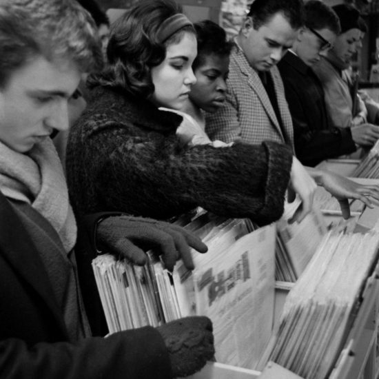 A crowd of young people stand in a record store in London in 1962 looking through racks of vinyl LP's