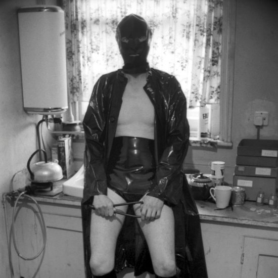 Male rubber fetishist and sex worker wearing his gear in the kitchen of his flat in Notting Hill, in front of a 2-bar electric fire. He holds a whip and his face is obscured by a rubber balaclava