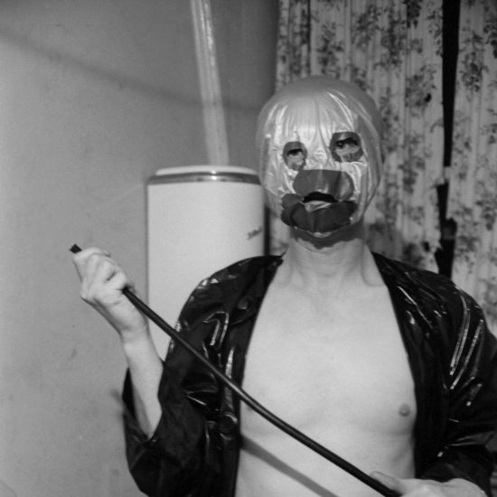 A male rubber fetishist and sex worker wearing his gear in the kitchen of his flat in Notting Hill, London. He holds a whip, his chest is bared and his face is obscured by a home-made mask; London, June 1964
