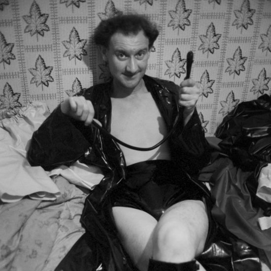 Male rubber fetishist and sex worker wearing his gear minus the mask in his flat in Notting Hill, sitting on a bed and holding a whip