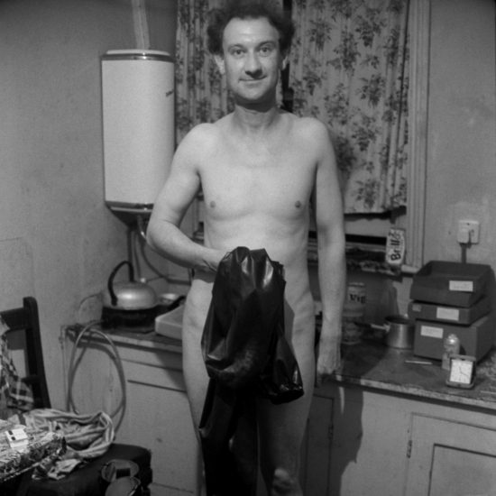 A naked male fetishist and sex worker holds his rubber suit in front of him in the kitchen of his flat in Notting Hill, London, June 1964